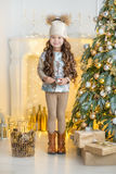 Child little girl with gift box near christmas tree and fireplace at home Royalty Free Stock Photo