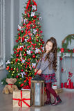 Child little girl with gift box near christmas tree and fireplace at home Stock Images