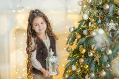 Child little girl with gift box near christmas tree and fireplace at home Royalty Free Stock Photos