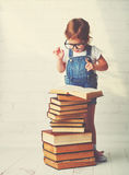 Child little girl with glasses reading a books Stock Image