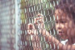 Child little girl hand holding steel mesh Stock Photography