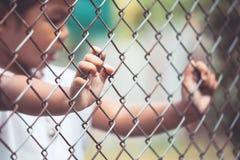 Child little girl hand holding steel mesh Royalty Free Stock Photo