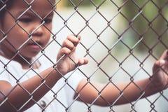 Child little girl hand holding steel mesh Stock Photos