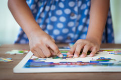 Child little girl hand trying to connect jigsaw puzzle piece Stock Photography