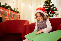 The child, a little girl in the hat of Santa Claus reading a boo Stock Photography