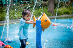 Child little girl having fun to play with water in park fountain royalty free stock photo