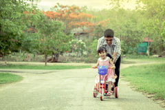 Child little girl having fun to ride tricycle with family Stock Images