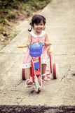 Child little girl having fun to ride tricycle with sister Stock Image
