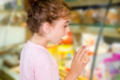 Child little girl looking in food shop display Royalty Free Stock Photo