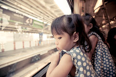 Child little girl looks in train window. In vintage color filter Stock Photo