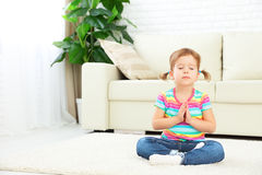 Child little girl meditates in lotus position and practices yoga Royalty Free Stock Photos