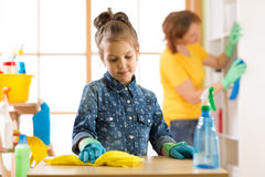 Child little girl and mother cleaning living room at home Royalty Free Stock Image