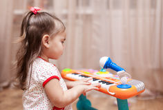 Child little girl playing on a toy piano Royalty Free Stock Photography