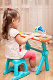 Child little girl playing on a toy piano Royalty Free Stock Photo