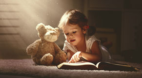 Child little girl reading a magic book in dark home. Child little girl reading a magic book in the dark home with a toy teddy bear stock photos