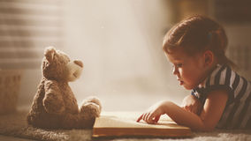 Child little girl reading a magic book in dark home. Child little girl reading a magic book in the dark home with a toy teddy bear stock image