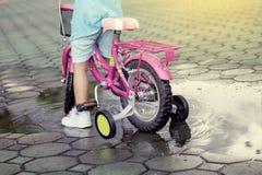 Child little girl riding bike in park Stock Photo