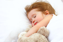 Child little girl sleeps in the bed with teddy bear Stock Photos
