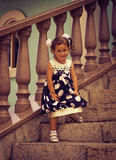 A child, a little girl. The child, a little girl standing on the steps of the porch Stock Photos