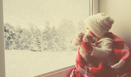Child little girl with  teddy bear at window and looking at wint Stock Photos
