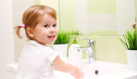 Child little girl washes her hands in bathroom Royalty Free Stock Photography