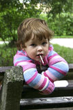 Child with lollipop. Child sitting on a bench with lollipop Stock Photo
