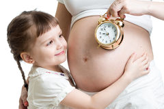 Child looking at alarm clock and pregnant woman belly Stock Photography