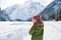 Child looking back while standing in front of snowy mountains Stock Photo