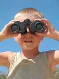 Child looking through binoculars. On a beach stock images