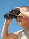 Child looking through binoculars. On a beach royalty free stock images