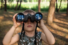 Child looking through binoculars. In the forest Stock Images