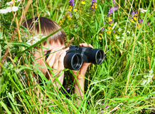 Child looking through binoculars. Boy hiding in grass looking through binoculars outdoor royalty free stock photography