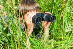 Child looking through binoculars stock photo