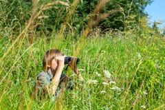 Child looking through binoculars stock photography