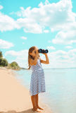 Child looking through binoculars in the expanse. Of the sea royalty free stock images