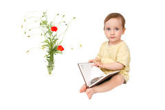 The child is looking through the book for records Royalty Free Stock Images
