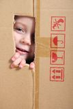 Child looking from box. Young girl looking from brown carton box Stock Images