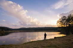 Child looking at bright sunset over lake Stock Photography