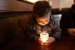 Child looking at candle Stock Photo