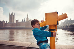 Child looking through coin operated binoculars. Child looking through coin operated high powered binoculars. View of the Palace of Westminster from the Thames stock photography