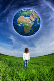 Child looking at the Earth planet. Against blue sky and spring green field. Elements of this image furnished by NASA stock image
