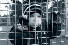 Child looking through fence. Sad alone child looking through fence Royalty Free Stock Photo