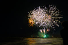 Child looking fireworks reflecting in the water in Forte dei Mar Stock Photography