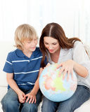 Child looking at a globe with his mother Stock Photography