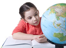 Child looking at globe. Child sitting with book and looking at rotating globe Stock Photo
