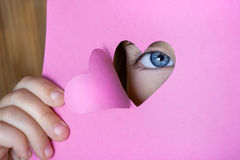 Child looking through a heart shape card Royalty Free Stock Photo
