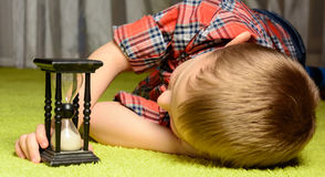 Child  looking at hourglass Royalty Free Stock Images