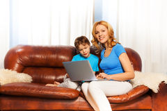 Child looking at laptop with smiling mum Stock Photo