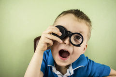 Child looking through a magnifying glass. Funny boy looking through a magnifying glass eye Stock Photo