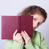 Child looking out of the book Royalty Free Stock Photos